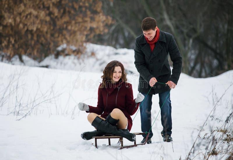 在雪撬的年轻夫妇骑马 图库摄影