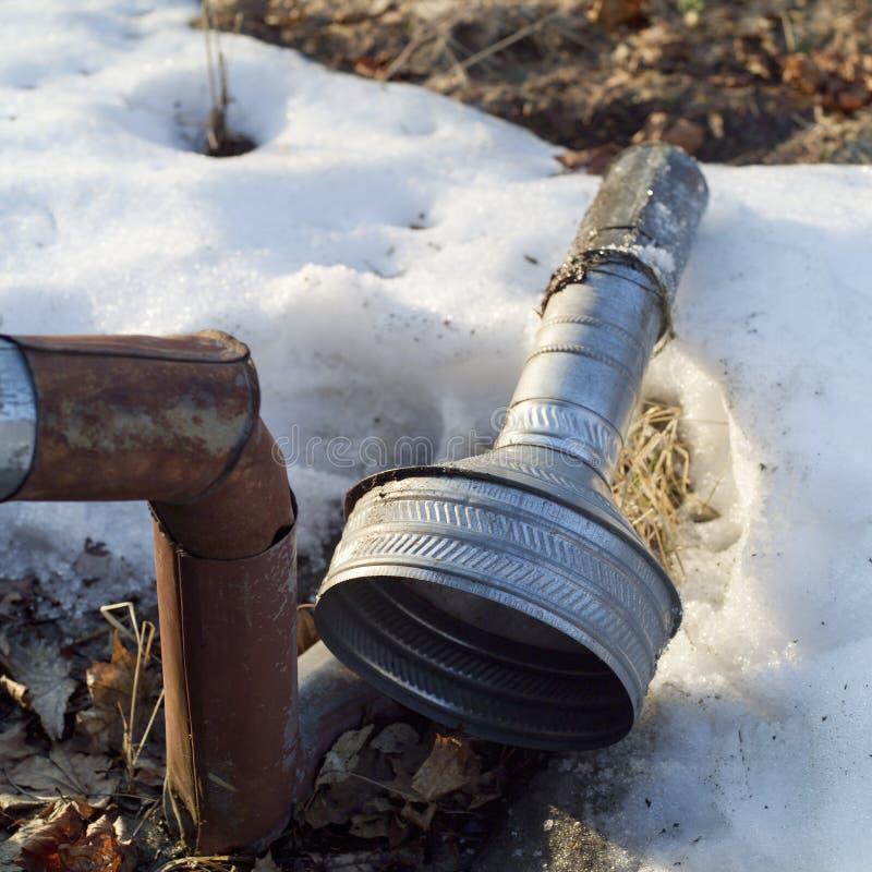 在雪放置的损坏的水落管 库存图片