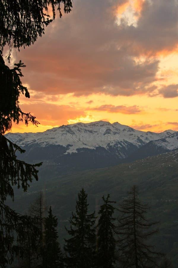 在雪日落的包括的山 库存照片