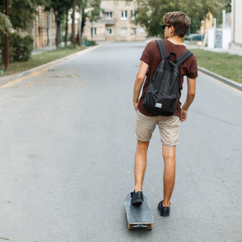 在雪板的年轻英俊的人乘驾 回到视图 免版税图库摄影