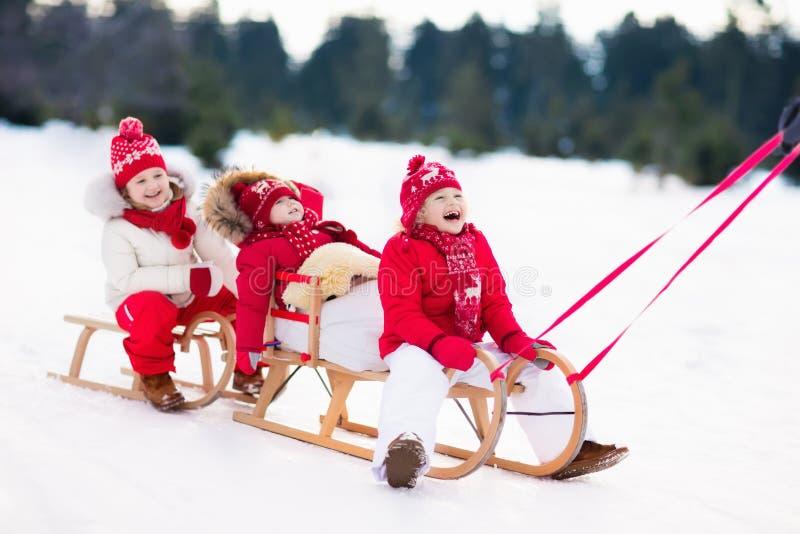 在雪橇的孩子 儿童雪撬 冬天雪乐趣 免版税库存图片