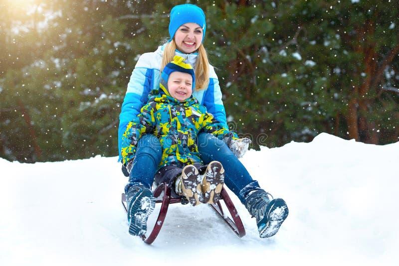在雪橇的母亲和儿子乘驾 在多雪的森林室外冬天乐趣的儿童游戏为家庭圣诞节假期 库存图片