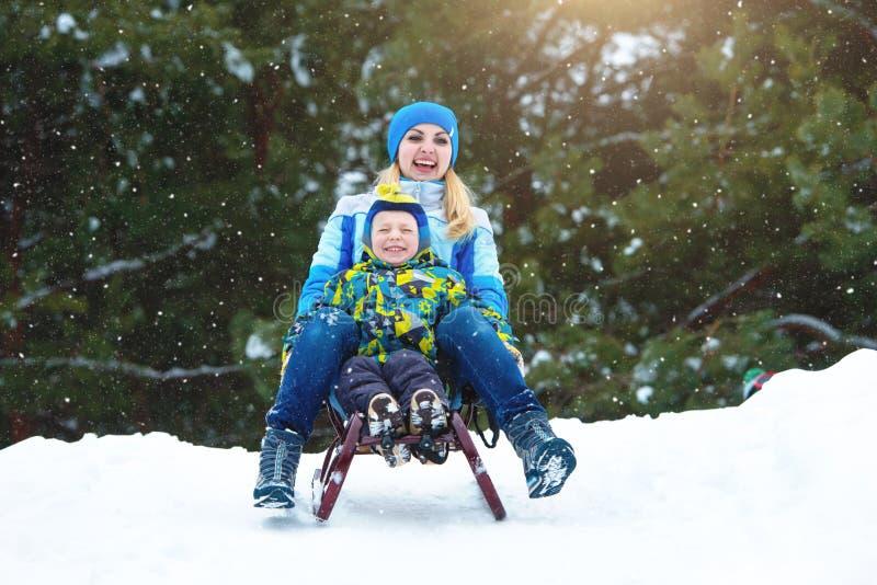 在雪橇的母亲和儿子乘驾 在多雪的森林室外冬天乐趣的儿童游戏为家庭圣诞节假期 图库摄影