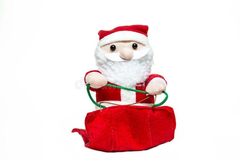 在雪橇的玩偶圣诞老人项目在白色背景 快活的圣诞节 前面 库存图片
