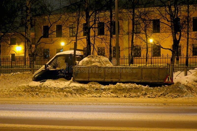 在雪清扫的路旁的停放的汽车 免版税库存照片