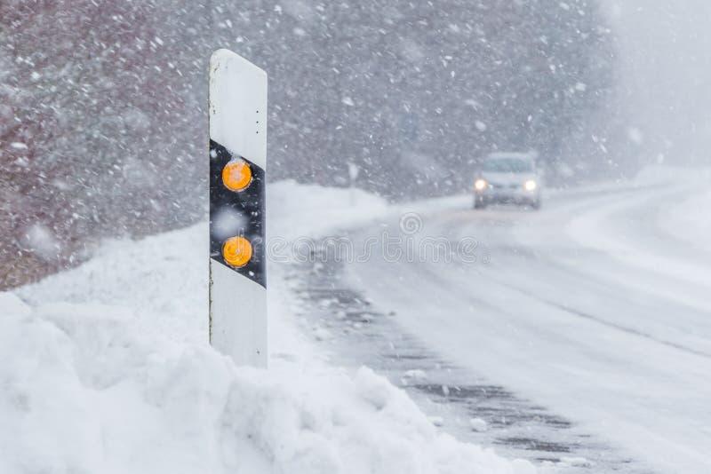在雪白色雪飞雪汽车冬天路的反射器岗位 库存照片