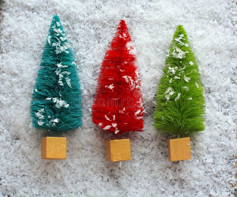 在雪的三棵五颜六色的圣诞树 库存照片