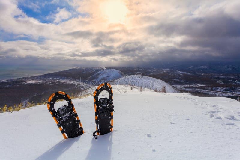 在雪的专业雪靴在冬天山和天空有云彩背景 snowplowing的 免版税图库摄影