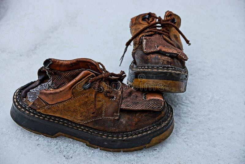 在雪的两老褴褛棕色起动 库存照片