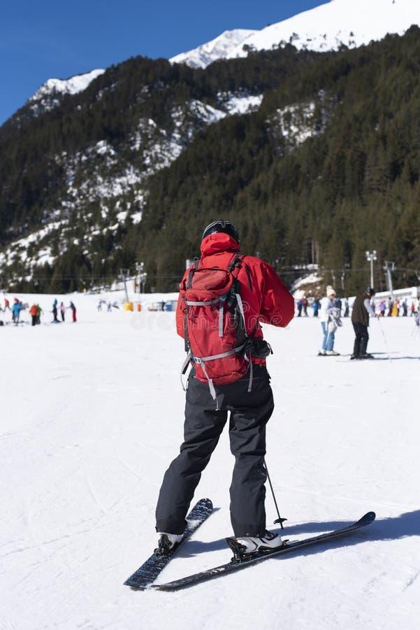 在雪的人滑雪在冬天 在红色黑滑雪的齿轮打扮的年轻人 在Bunderishka polyana的天空,滑雪倾斜的滑雪者, 图库摄影