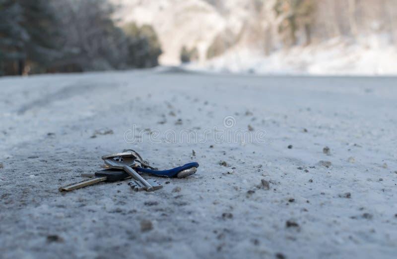 在雪的冬天丢失了说谎在路一边的一个钥匙串 免版税库存图片