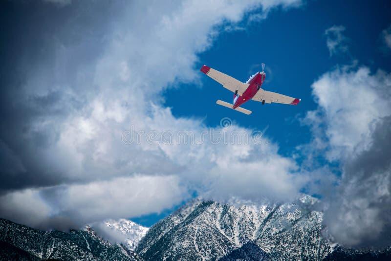 在雪的单引擎平面飞行加盖了山 免版税库存照片