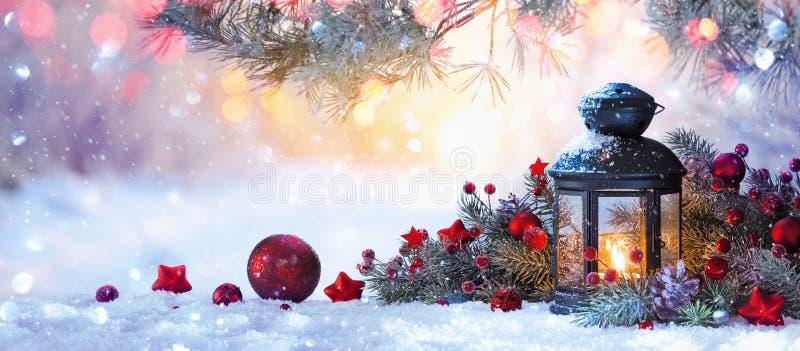 在雪的圣诞节灯笼与冷杉分支在阳光下 免版税库存照片