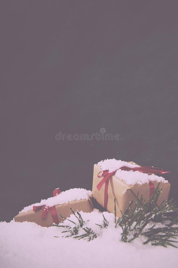 在雪的圣诞节礼物反对黑板葡萄酒减速火箭的Fi 库存照片