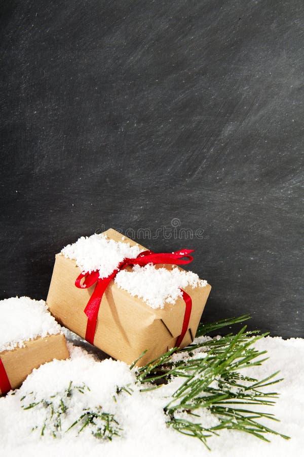 在雪的圣诞节礼物反对黑板 免版税库存图片