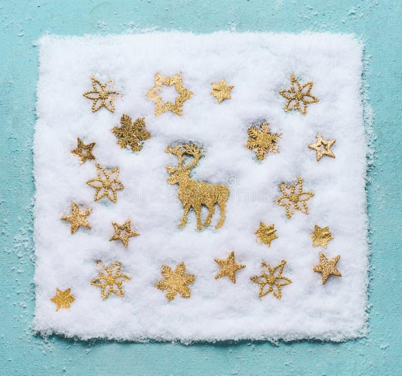 在雪的圣诞节驯鹿与在浅兰的背景,顶视图的金黄雪花 平的位置 库存图片