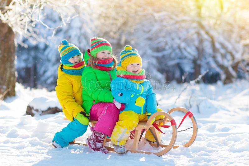 在雪的孩子戏剧 冬天孩子的雪撬乘驾 免版税图库摄影