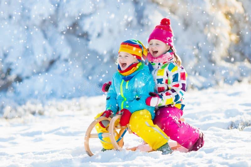 在雪的孩子戏剧 冬天孩子的雪橇乘驾 免版税库存图片
