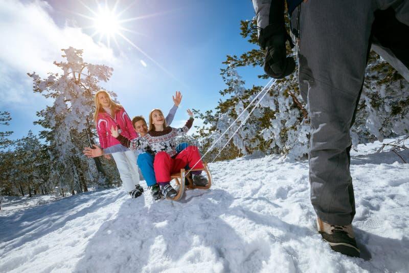 在雪的家庭获得乐趣sledding在晴朗的冬日 库存图片