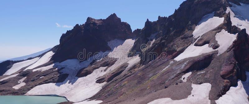 在雪的山由湖 库存照片