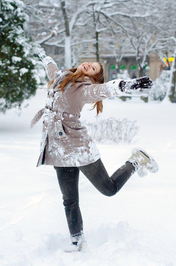 在雪的愉快的十几岁的女孩跳舞 免版税库存照片