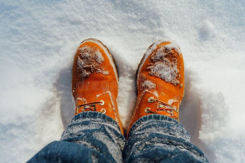 在雪的橙色冬天鞋子 免版税库存照片