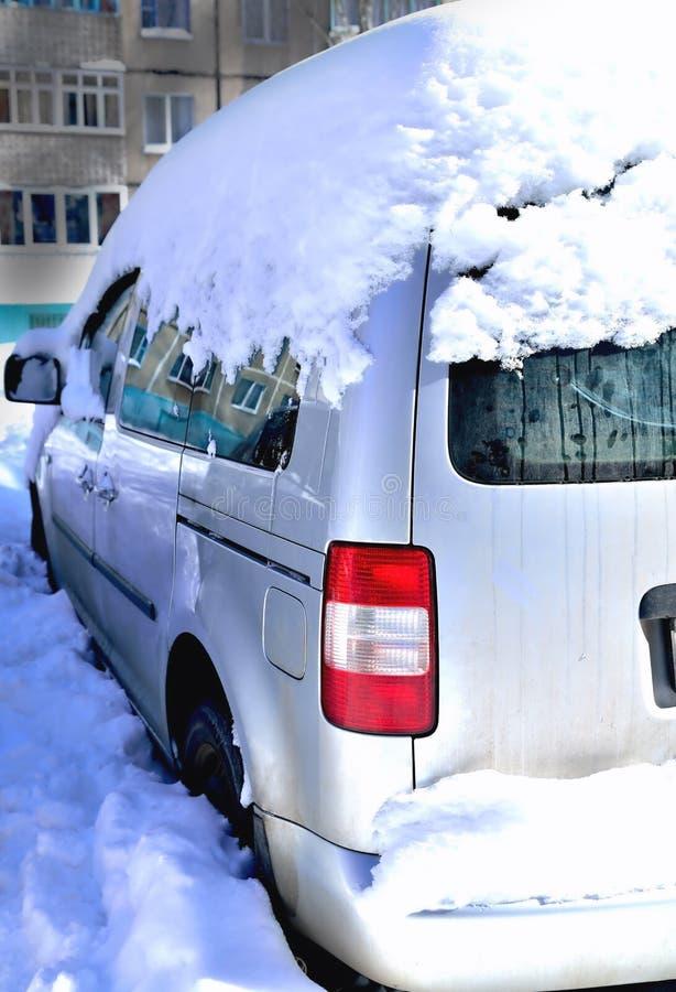 在雪的汽车以房子在一好日子,雪,在玻璃的反射大随风飘飞的雪为背景  库存照片