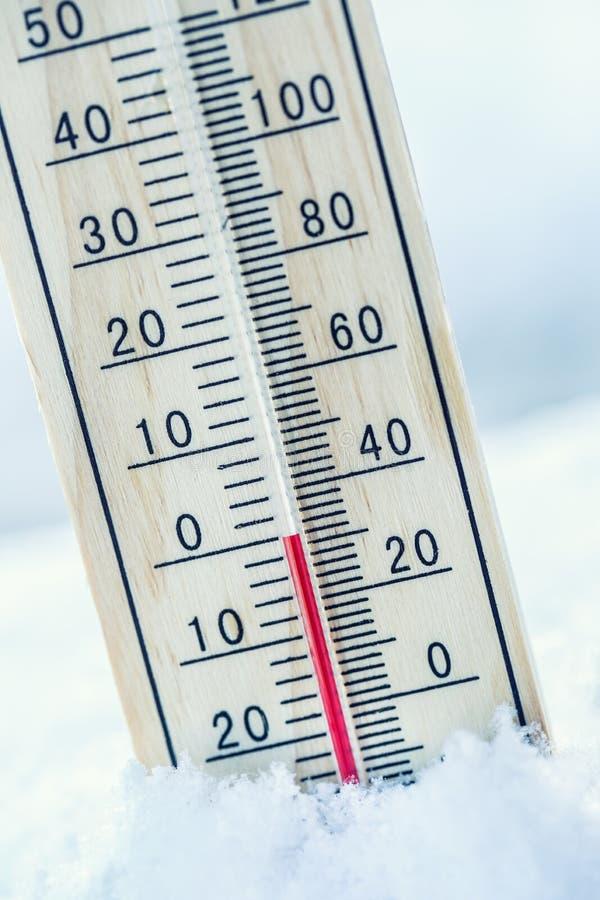在雪的温度计显示低温零 低温 免版税图库摄影