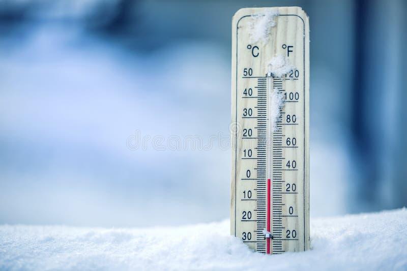 在雪的温度计显示低温-零 在摄氏度和华氏低温 冷的冬天天气-零 免版税库存图片