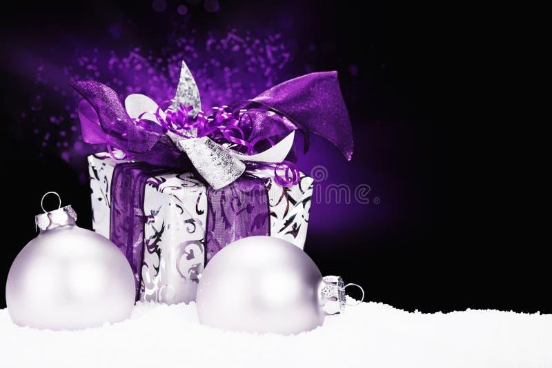 在雪的紫色圣诞节礼物 免版税图库摄影