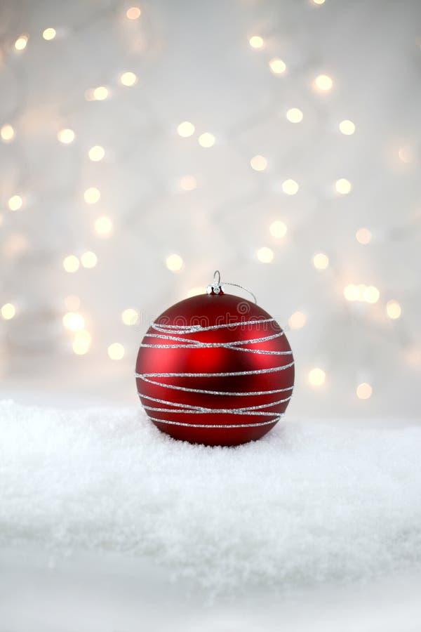 在雪的红色假日电灯泡 库存图片