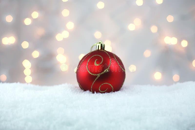 在雪的红色假日电灯泡 免版税库存图片