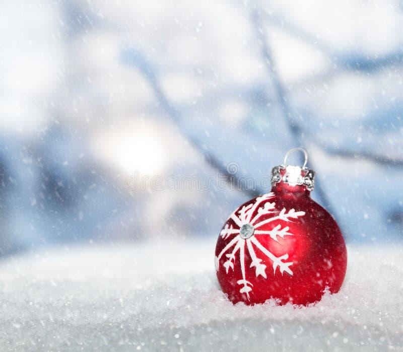 在雪的红色圣诞节球反对降雪的冬天风景 免版税库存照片