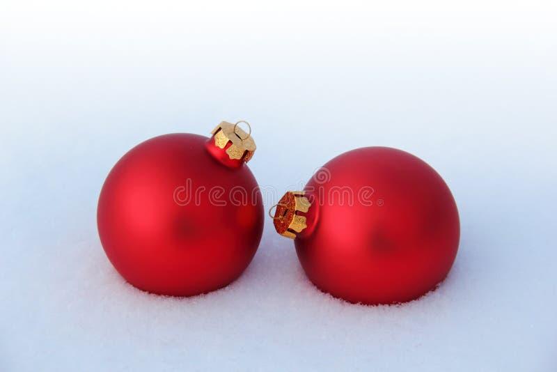 在雪的红色圣诞节球 免版税库存照片