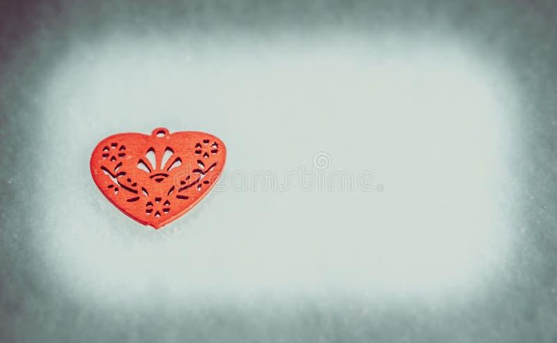 在雪的红色木心脏 免版税库存照片
