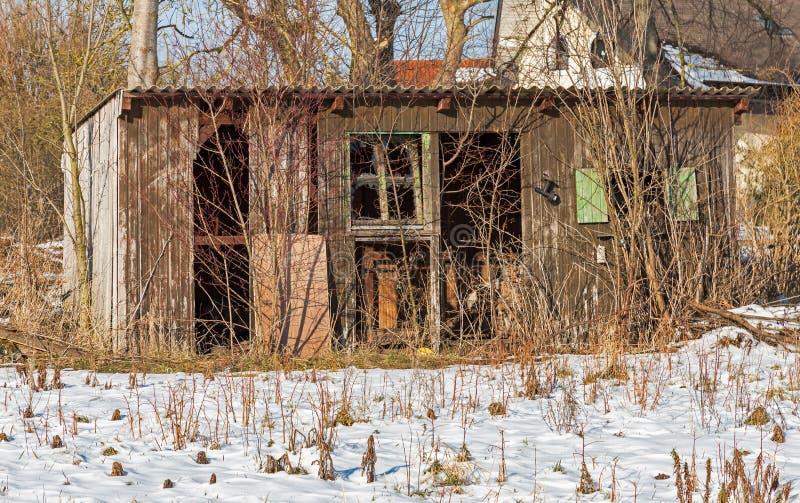 在雪的老被毁坏的小屋 免版税库存照片