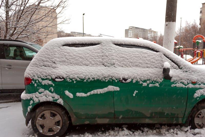 在雪的肮脏的绿色小型客车不可以是 第一降雪 在雪盖的汽车在城市 运输问题,不足 库存照片