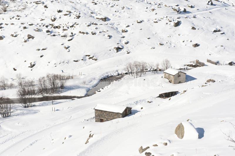 在雪的被隔绝的山小屋 库存图片