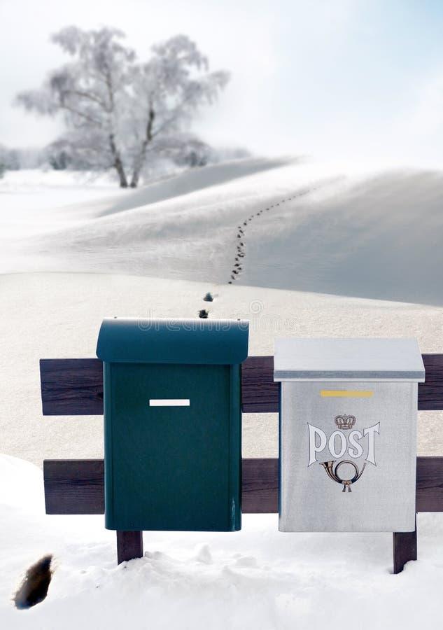 在雪的邮件配件箱和脚印 免版税库存图片