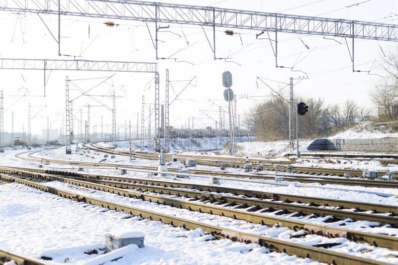 在雪的铁轨 商品铁货车,冬天 在铁路轨道上的高压导线 美好的日落光 免版税库存照片