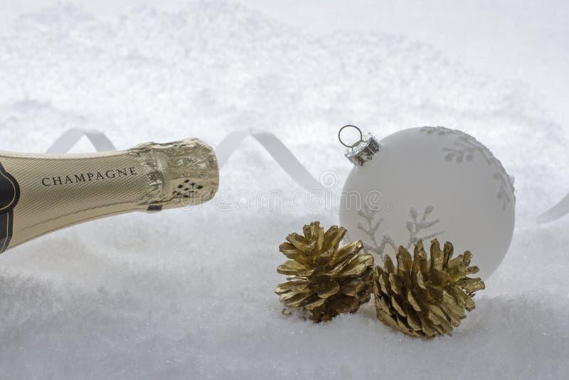 在雪的香宾瓶与圣诞树球 库存照片