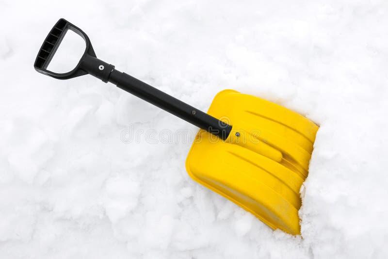 在雪的黄色雪铁锹 免版税库存照片