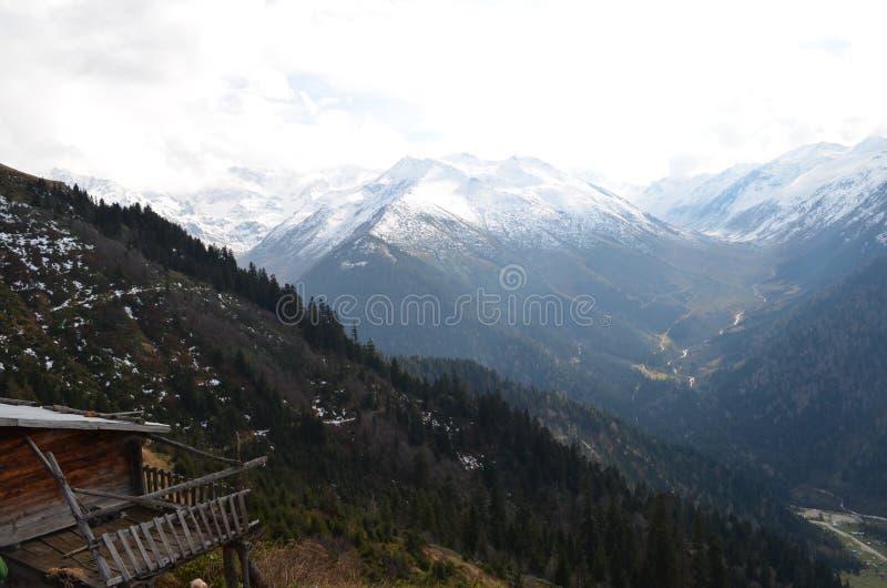 在雪盖的山用云彩在背景中 免版税库存图片