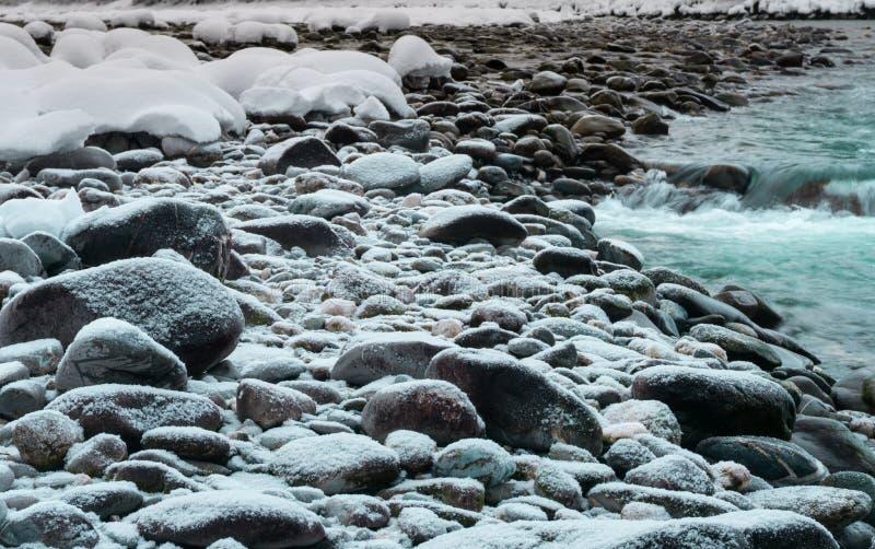 在雪盖的岩石在绿松石和怀特河的银行剥落 库存照片