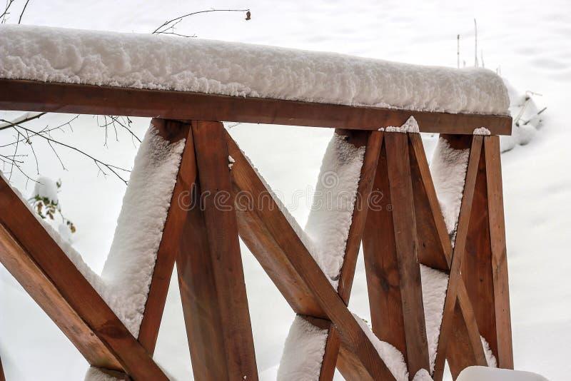 在雪盖的木露台甲板栏杆 库存照片