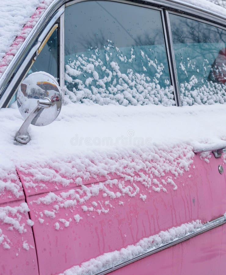 在雪盖的桃红色经典汽车 免版税图库摄影
