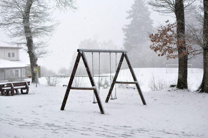 在雪盖的森林操场的木摇摆在冬天 库存图片