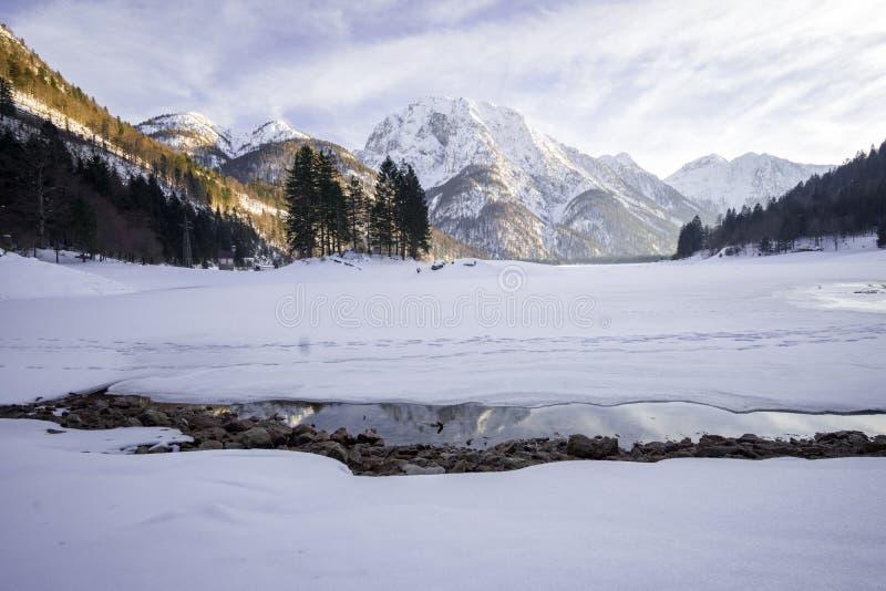 在雪盖的结冰的湖用在后面的多雪的山 图库摄影