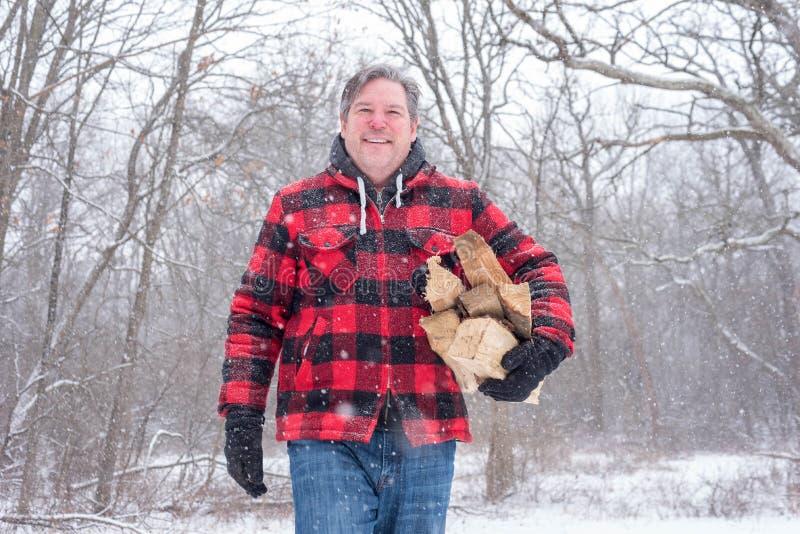 在雪盖的羊毛夹克的人带来木柴 免版税库存照片