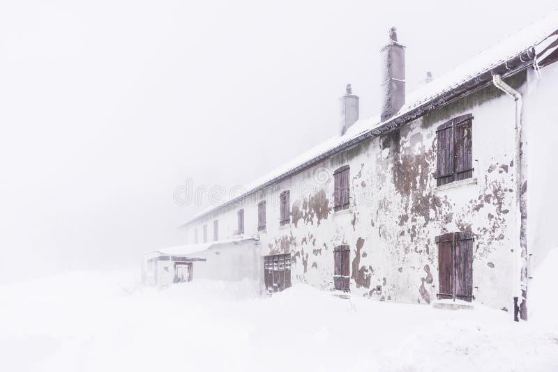 在雪盖的被撕毁的房子-水平 库存图片